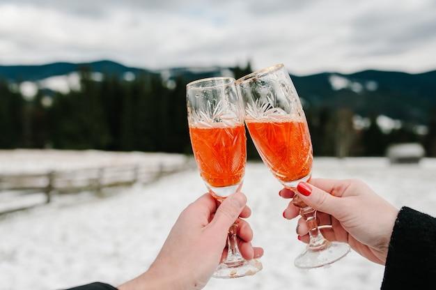 Homem e mulher têm nas mãos duas taças com champanhe nas montanhas de inverno.