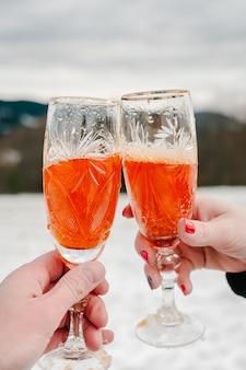 Homem e mulher têm nas mãos uma duas taças com champanhe no fundo das montanhas de inverno.