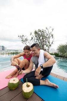 Homem e mulher tirando fotos de cocos após o treino de ioga