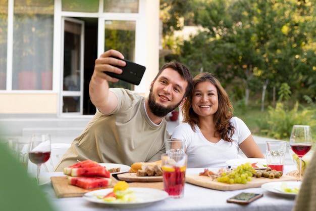 Homem e mulher tirando selfie em foto média
