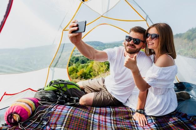 Homem e mulher tirando uma foto auto na barraca
