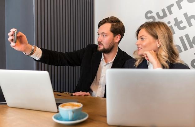 Homem e mulher tirando uma selfie em uma reunião