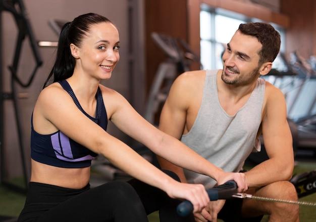 Homem e mulher tiro médio na academia