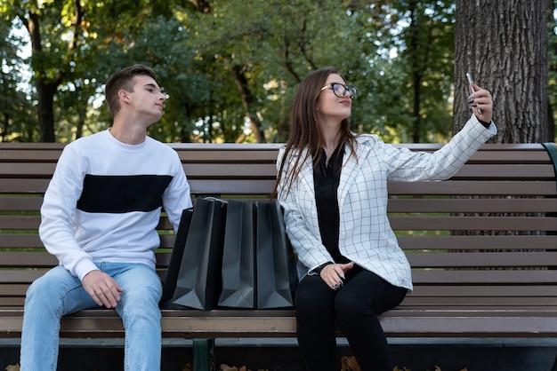 Homem e mulher tomam selfie no banco com sacolas de compras. jovem marido e mulher descansando depois de fazer compras no banco do parque.