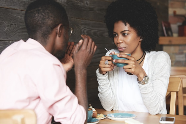 Homem e mulher tomando café no café