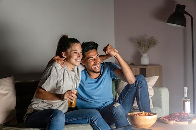 Homem e mulher tomando cerveja em casa enquanto assistem tv e comem lanches
