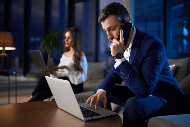 Homem e mulher trabalhando em laptops em casa