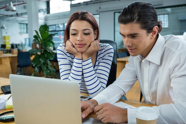 Homem e mulher trabalhando em um laptop na mesa