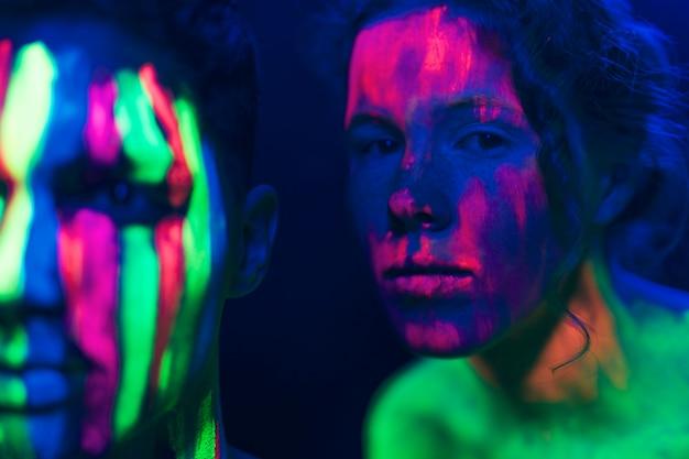 Homem e mulher usando maquiagem fluorescente