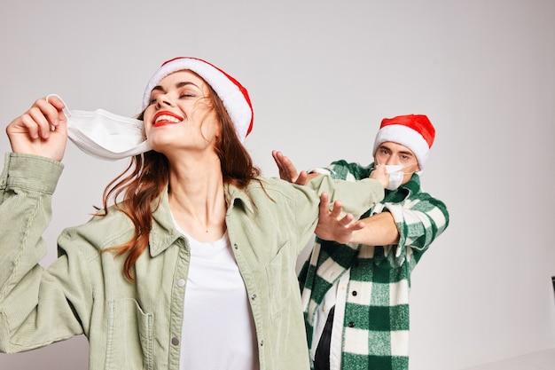 Homem e mulher usando máscaras médicas. celebração de natal no estúdio de ano novo