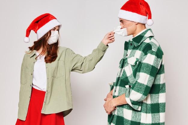Homem e mulher usando máscaras médicas, estúdio de proteção de férias de ano novo