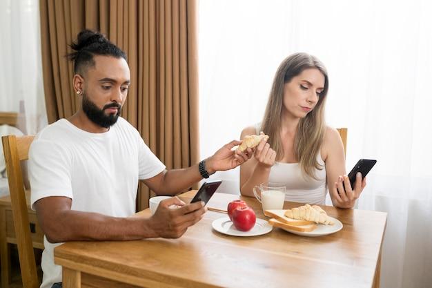 Homem e mulher usando o telefone na cozinha