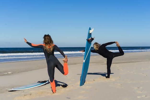 Homem e mulher vão ao oceano com pranchas de surf. homem e menina vão surfando