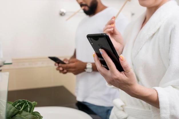 Homem e mulher verificando seus telefones até no banheiro
