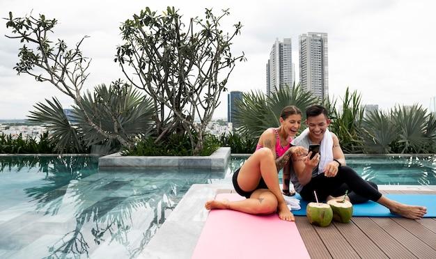 Homem e mulher verificando smartphone após sessão de ioga