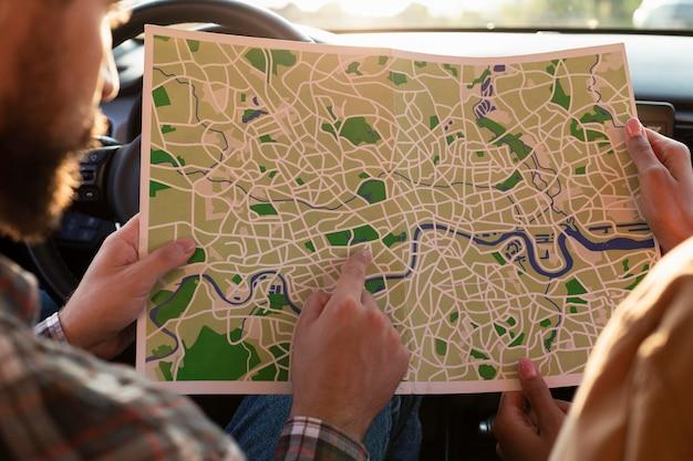 Homem e mulher verificando um mapa no carro