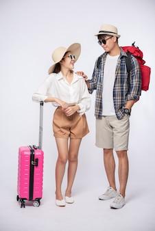 Homem e mulher vestidos de óculos para viajar com malas