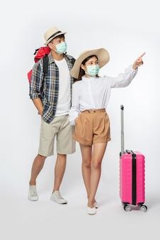 Homem e mulher vestidos para viajar, usando máscaras junto com a bagagem