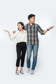 Homem e mulher vestindo camisas e alegremente estendendo as mãos para o lado