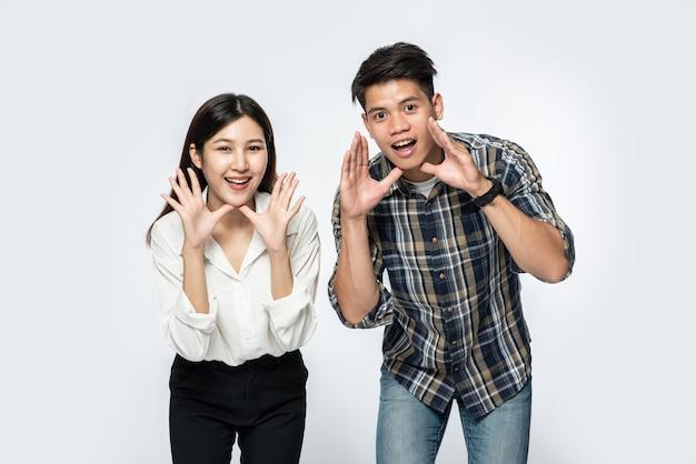Homem e mulher vestindo camisetas e fazendo as mãos gritando parabéns