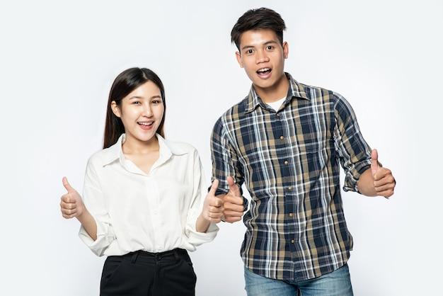 Homem e mulher vestindo camisetas e fazendo sinais com as mãos levantando os polegares