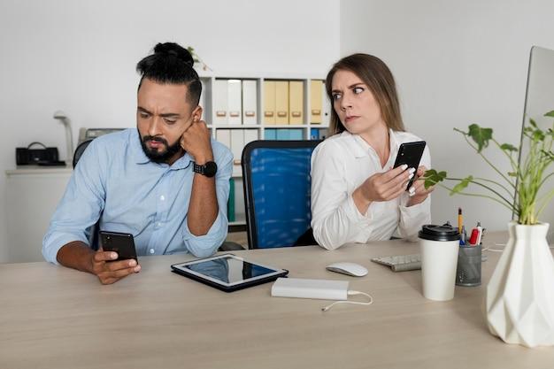 Homem e mulher viciados em seus telefones