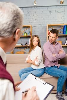 Homem e mulher zangados sentados de costas um para o outro em uma recepção no psicólogo