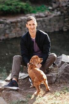 Homem e pastor da ásia central passear no parque. ele mantém o cachorro na coleira.