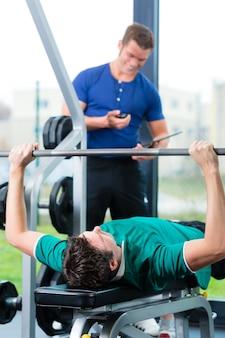 Homem e personal trainer no ginásio