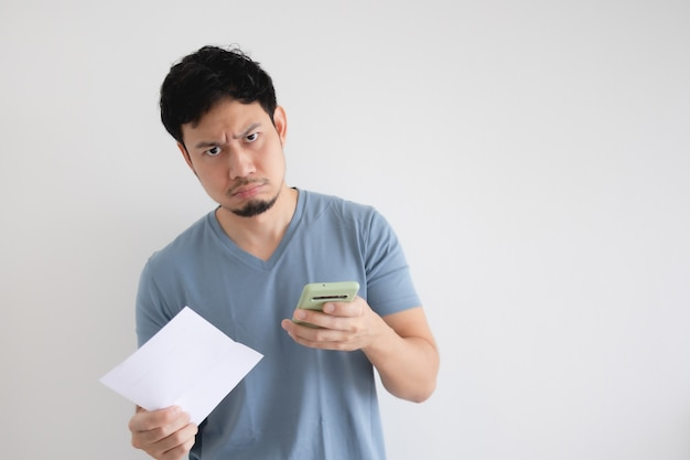 Homem é sério pela conta e o smartphone na parede isolada.