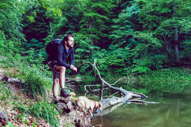 Homem e seu cachorro descansando na margem do lago