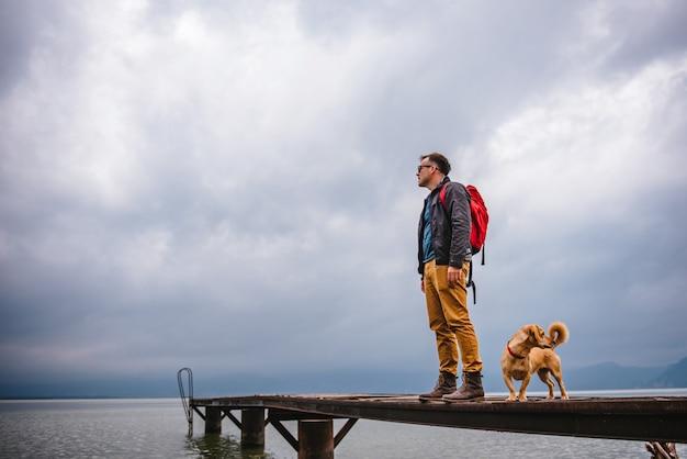 Homem e seu cachorro em pé na doca de madeira