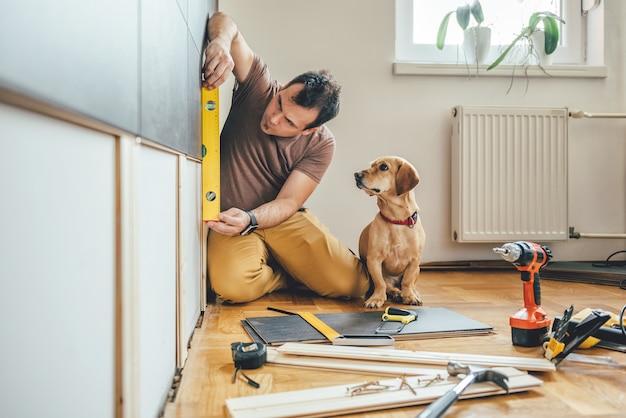 Homem e seu cachorro fazendo trabalhos de renovação em casa