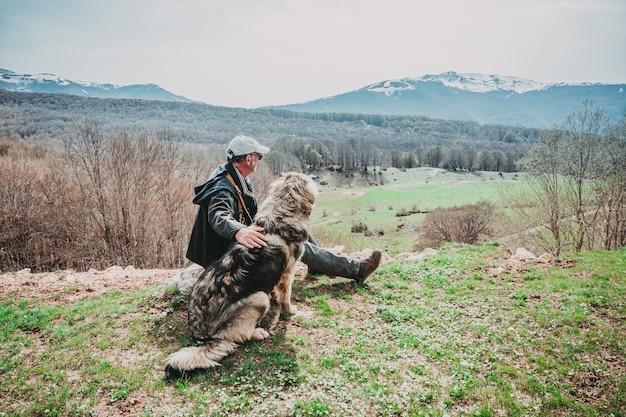 Homem e seu cão sentado olhando as montanhas