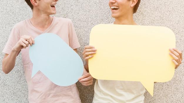 Homem e seus amigos segurando balões de fala
