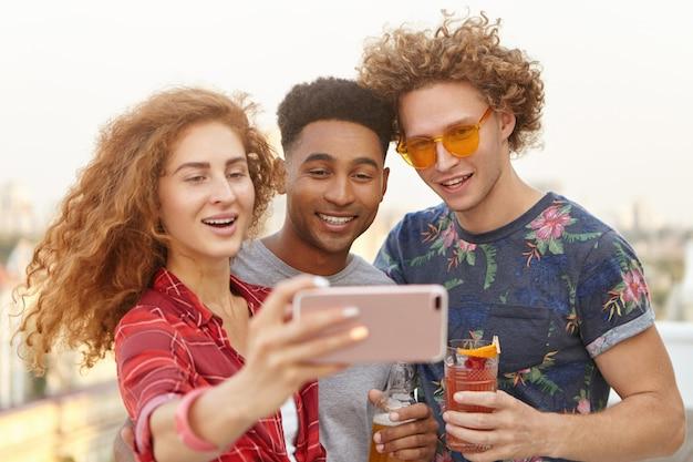 Homem e seus dois amigos com cabelo encaracolado tirando selfies