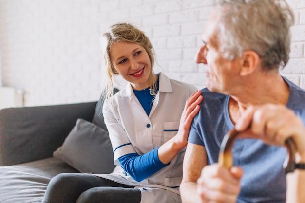 Homem e sorridente enfermeira no lar de idosos