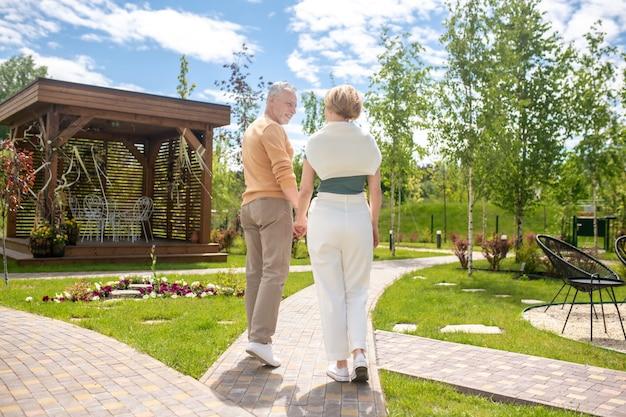 Homem e sua esposa passeando de mãos dadas