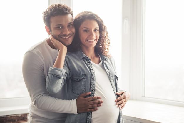 Homem e sua linda esposa grávida estão abraçando e sorrindo.