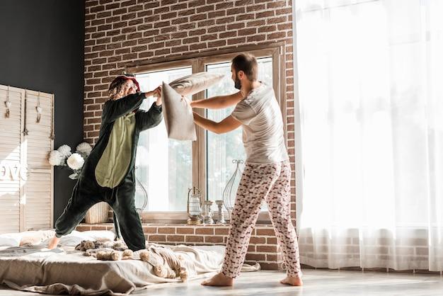 Homem e sua namorada em traje tendo engraçado travesseiro lutar em casa