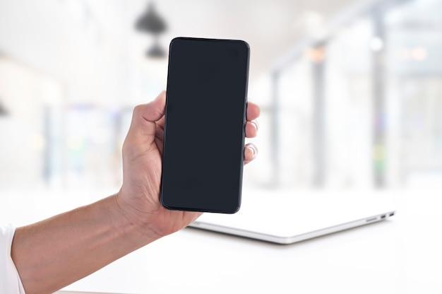 Homem e telefone móvel de tela em branco sobre fundo desfocado.