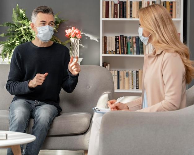 Homem e terapeuta usando máscaras