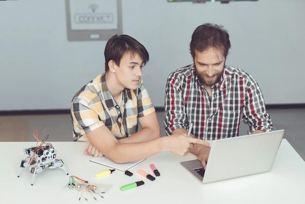 Homem e um adolescente estão sentados à mesa na frente do laptop