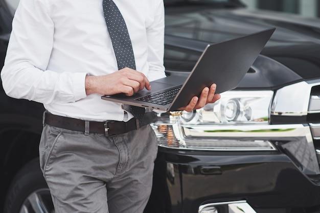 Homem é um homem que trabalha em um laptop e testa dispositivos móveis.