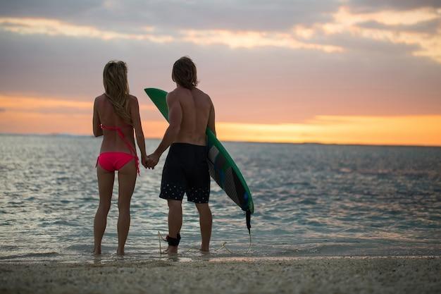 Homem e uma mulher com pranchas de surf ao pôr do sol