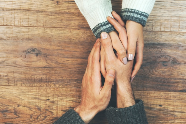 Homem e uma mulher de mãos dadas em uma mesa de madeira