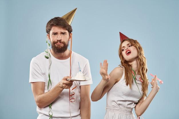 Homem e uma mulher em um aniversário com um bolinho e uma vela em um boné festivo se divertir e comemorar o feriado juntos, casal feliz