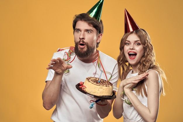 Homem e uma mulher em um aniversário com um bolinho e uma vela em um boné festivo se divertir e comemorar o feriado juntos