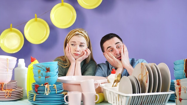 Homem e uma mulher em um fundo isolado têm pavor de muitos pratos sujos