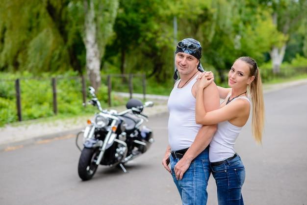 Homem e uma mulher estão abraçando perto de uma motocicleta na rua.